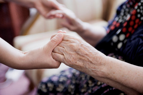 young hands holding elderly hands
