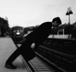 man leaning over a train track